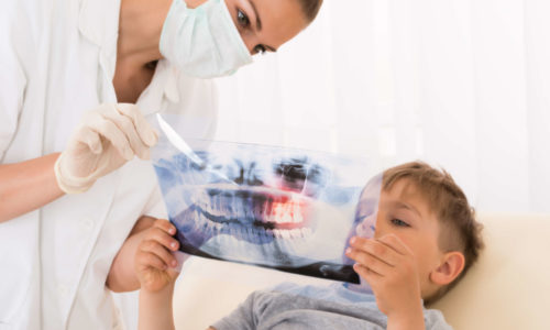 Orthodontist explains braces treatment to a child